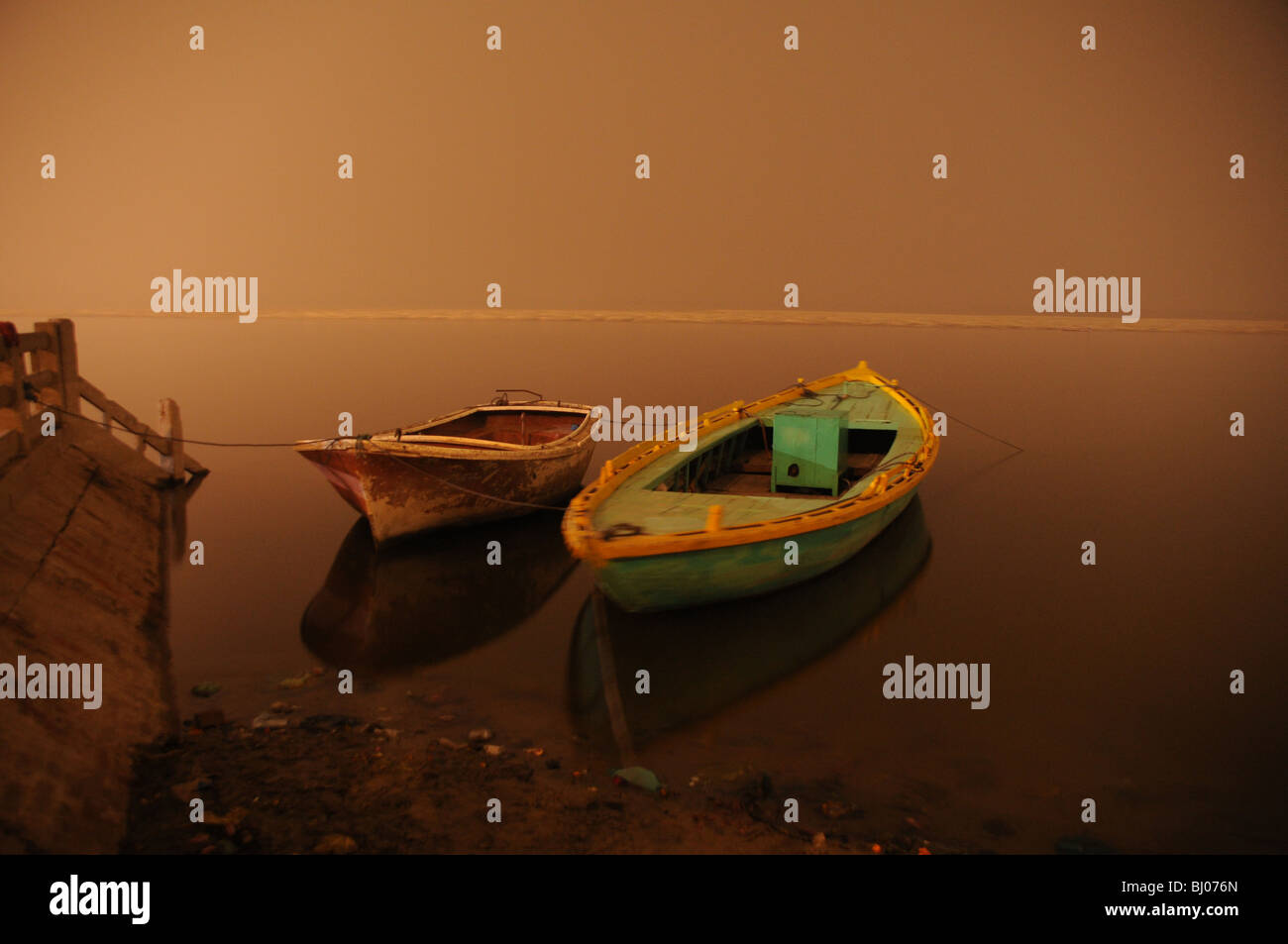 two boats float peacefully at the edge of the ganges river in varanasi, their reflections show the stillness of - Stock Image