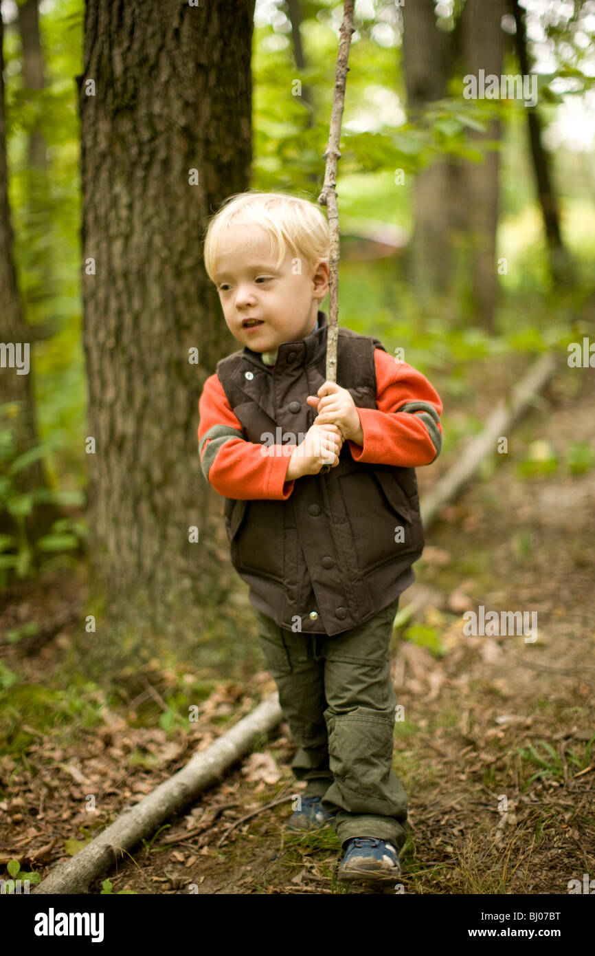 Young boy walking in the woods carrying a stick. - Stock Image
