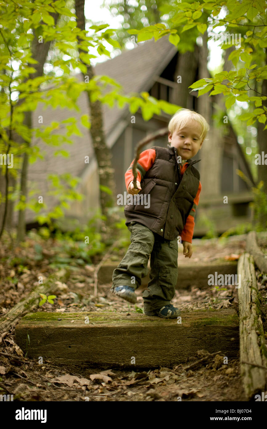 Young boy climbing down stairs in the woods, carrying a stick. Stock Photo