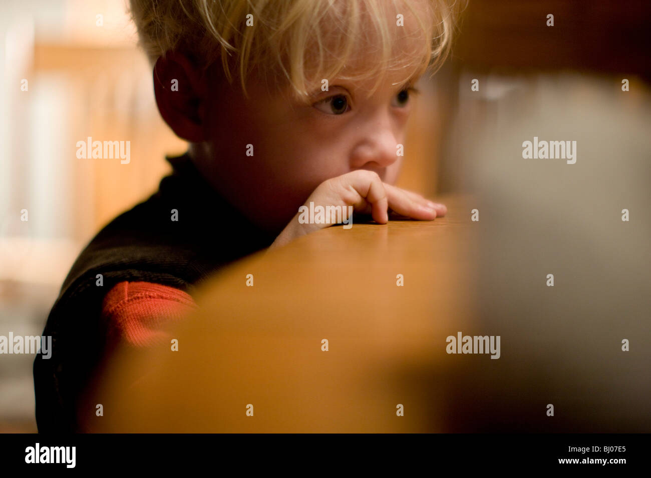 Young boy leaning on edge of table in thought. - Stock Image