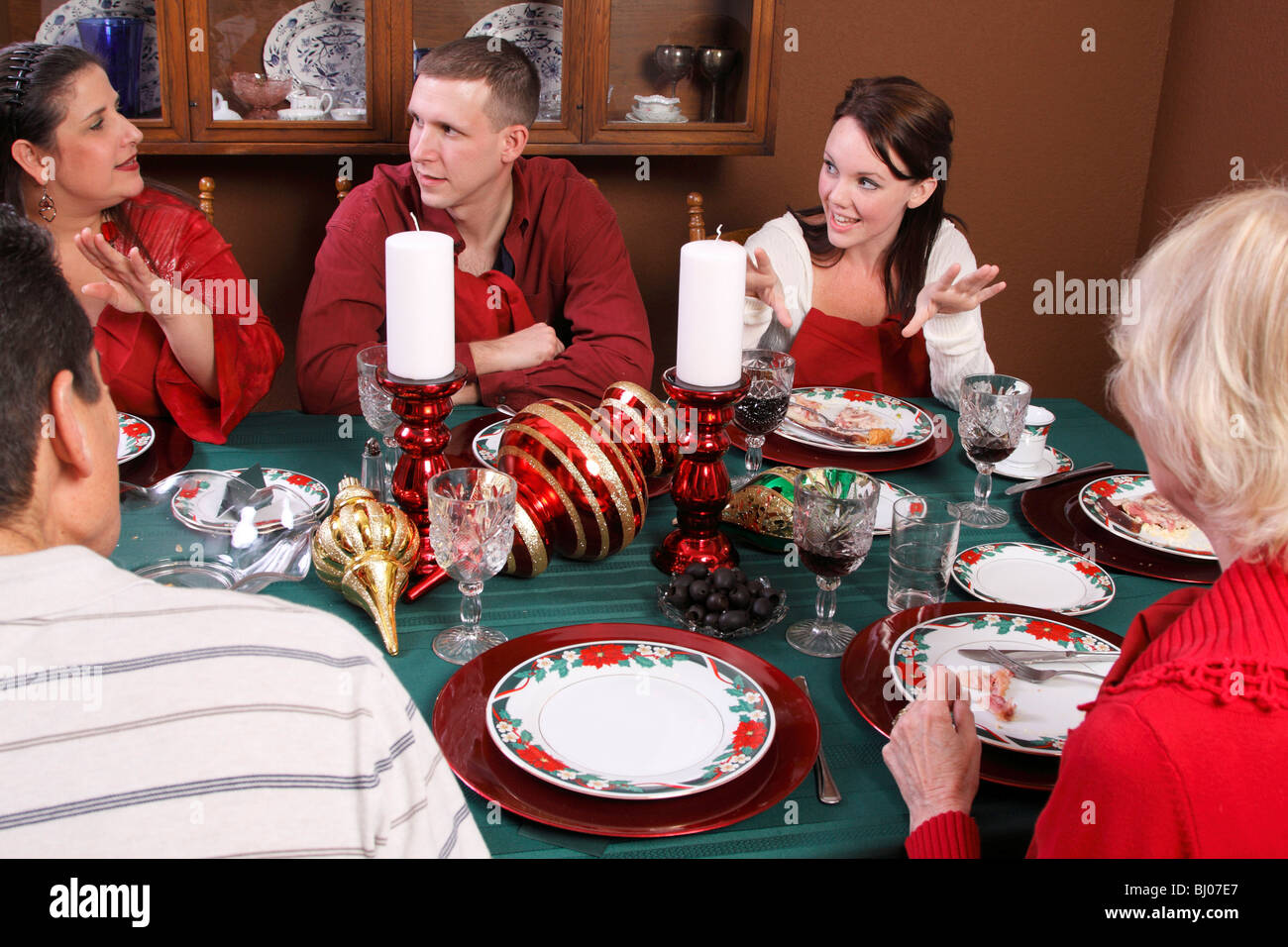Family sharing Christmas dinner and talking - Stock Image