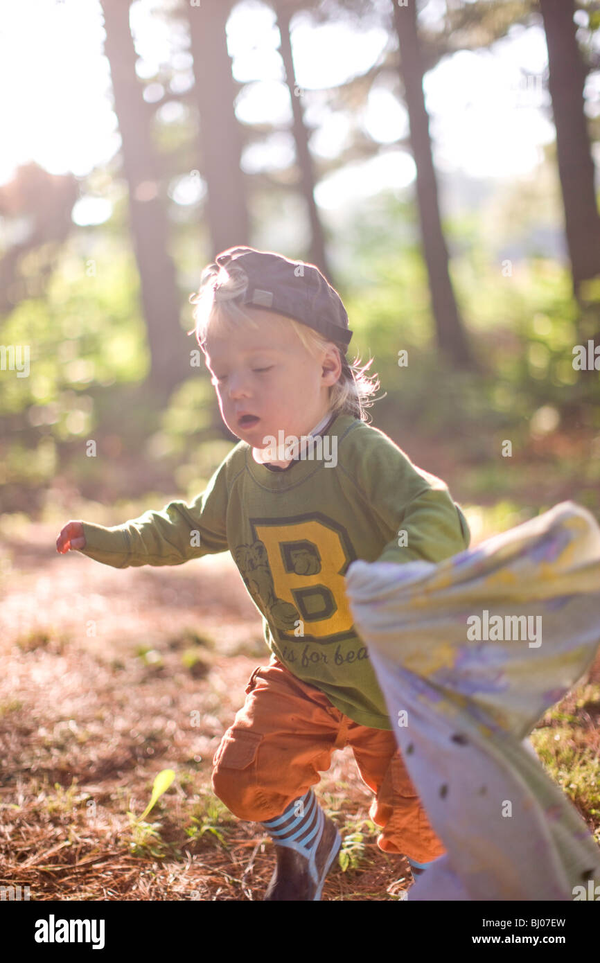 Young boy carrying a blanket in the woods. - Stock Image