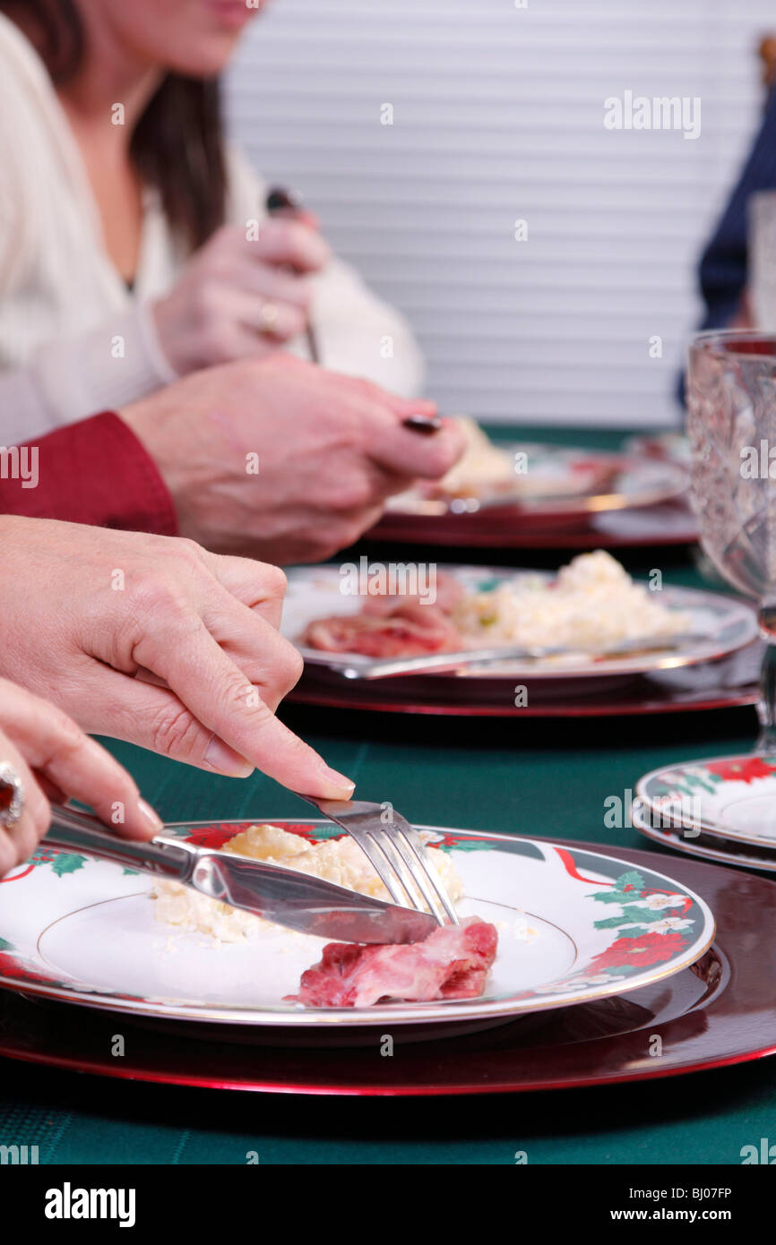 Someone cutting ham during Christmas dinner - Stock Image