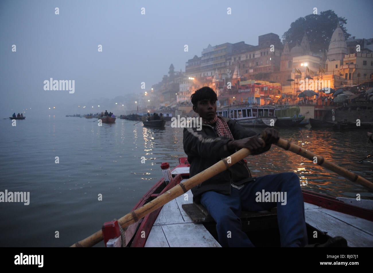 A young man rows past Varanasi's sacred ghats on the River Ganges just before sunrise - Stock Image