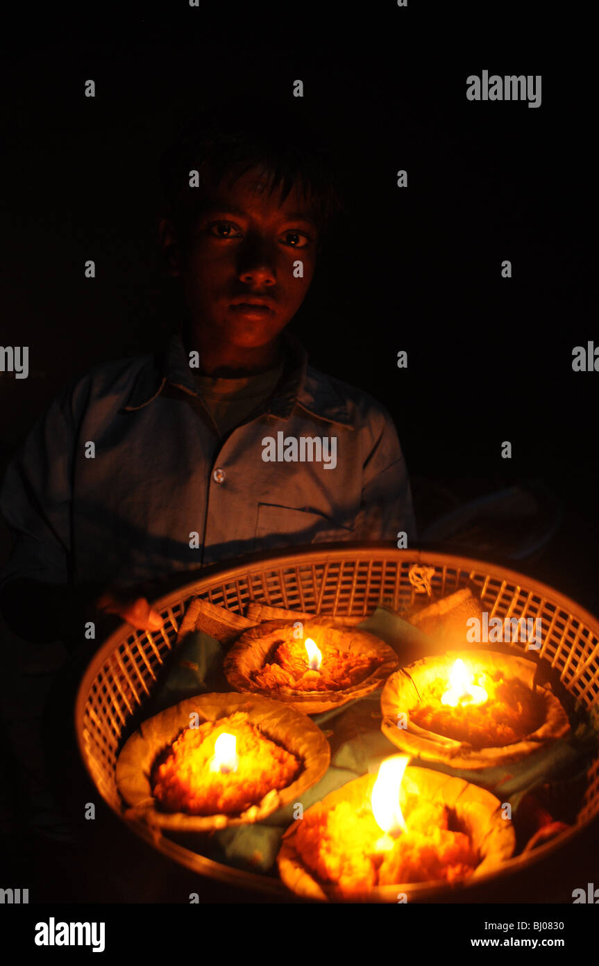 basket of candles, the fire lights a boy's face softly showing us his serious expression, age10, this is how - Stock Image