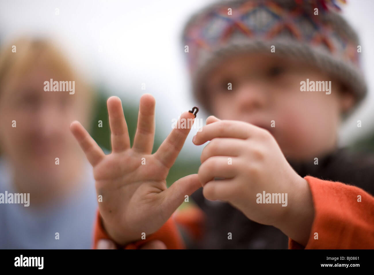 Young boy looking at an inchworm crawling on his hand. - Stock Image