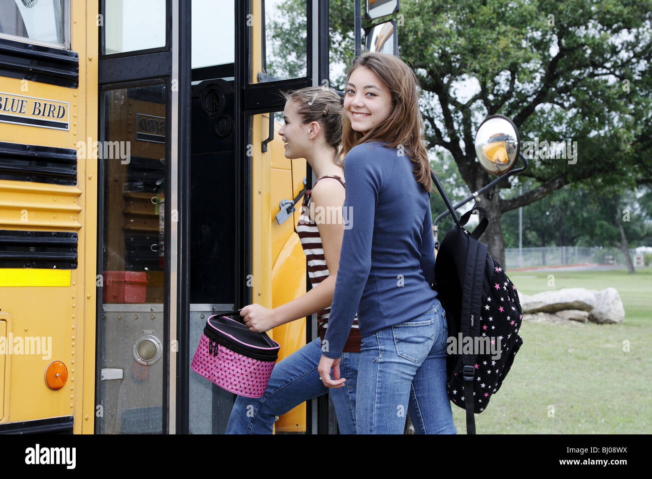 Students getting on a school bus - Stock Image