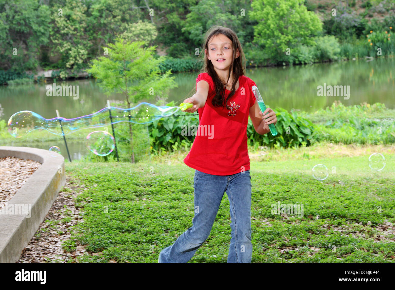 A young girl having fun playing with bubbles - Stock Image
