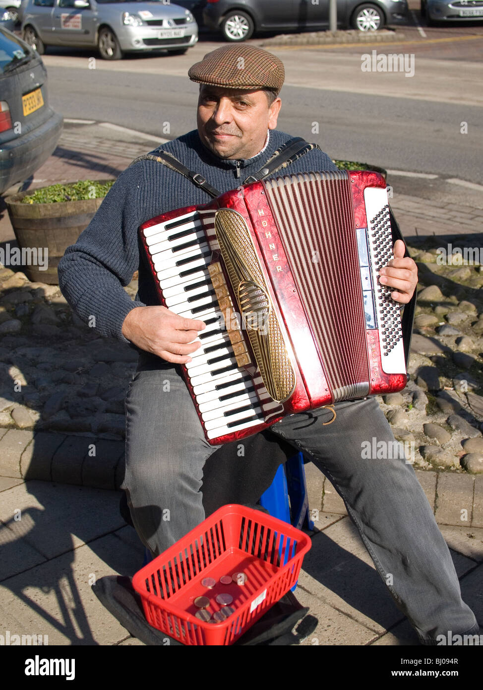 An Eastern European street musician playing a piano accordian in the spring sunshine in Northallerton North Yorkshire - Stock Image
