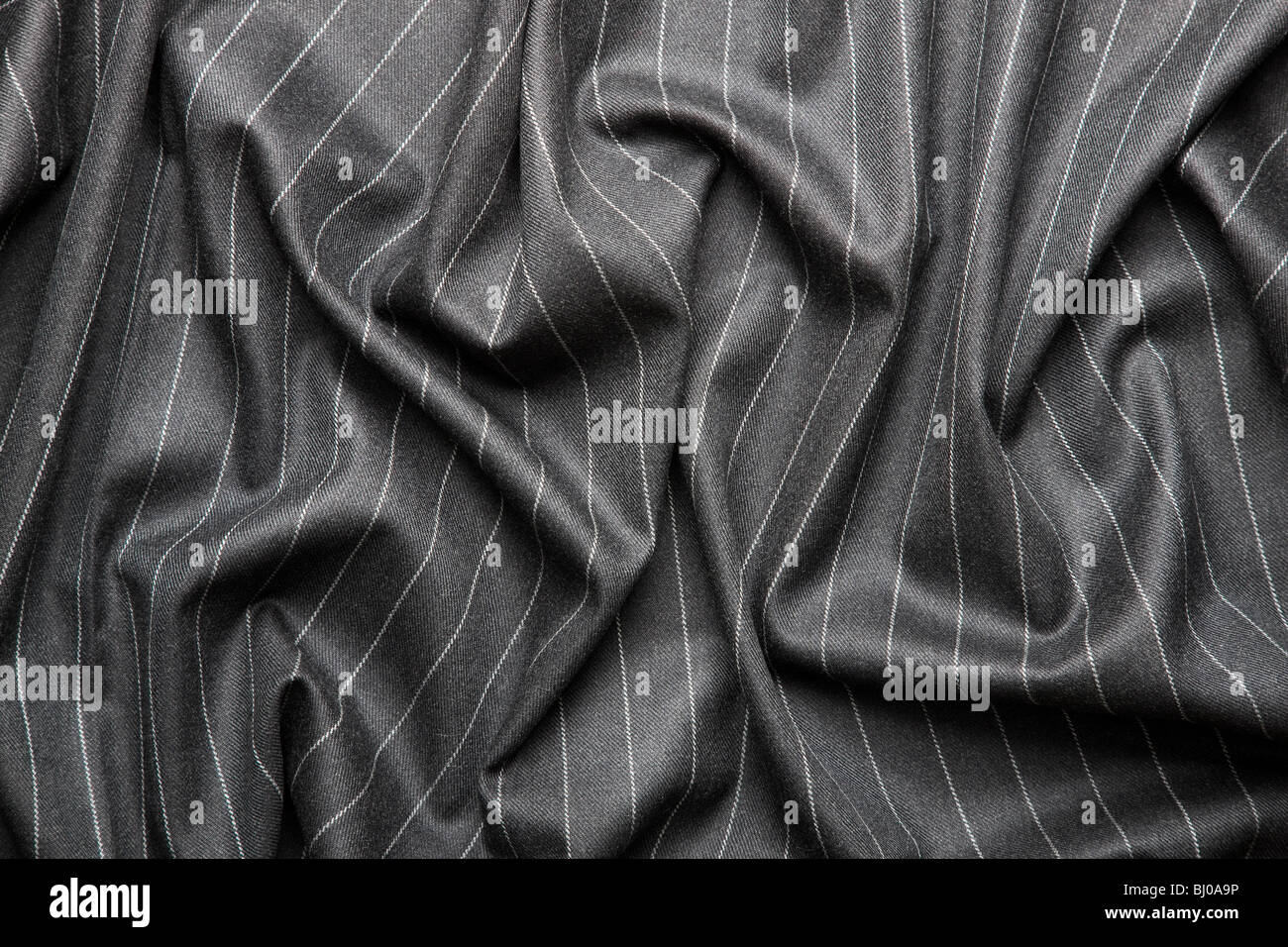 High quality pin stripe suit background texture with folds - Stock Image