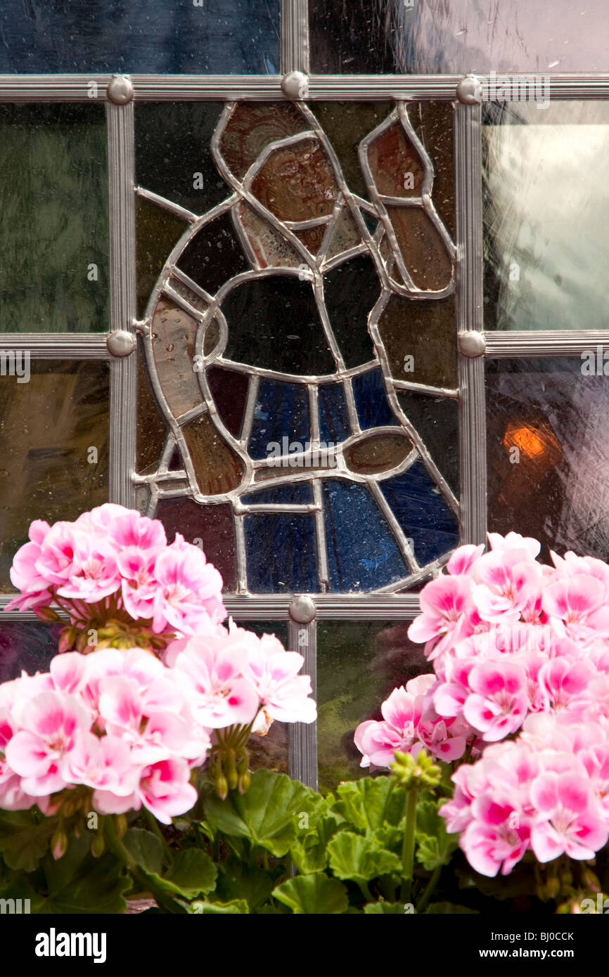 Stained glass window and flowers, Lohr am Main Germany - Stock Image