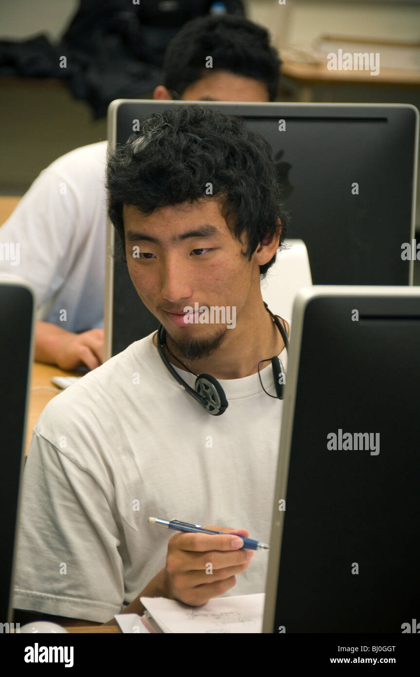 male Korean high school student working on a Mac computer in digital photography class. - Stock Image