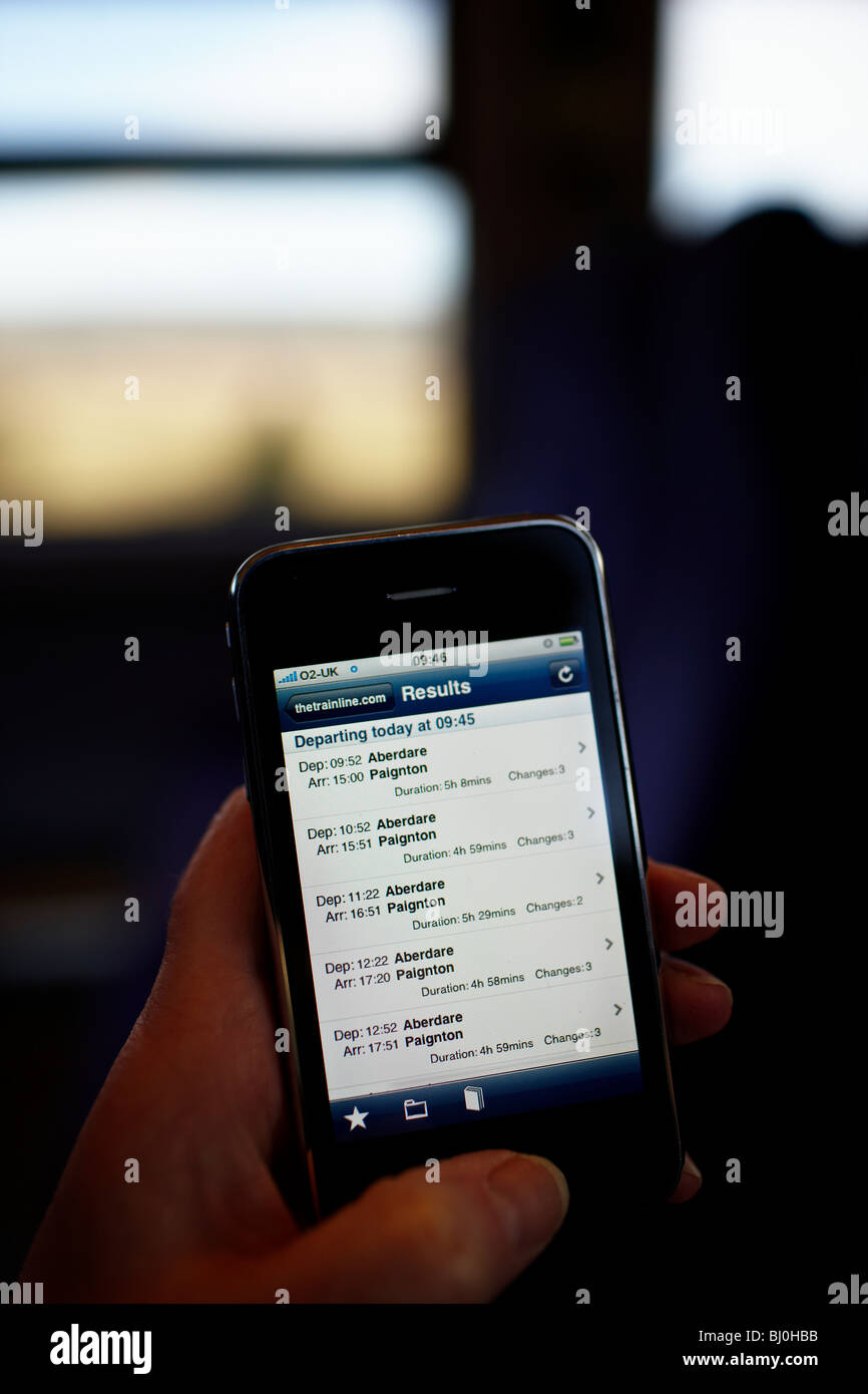 Using an iPhone on the train to get timetable information from an app. - Stock Image