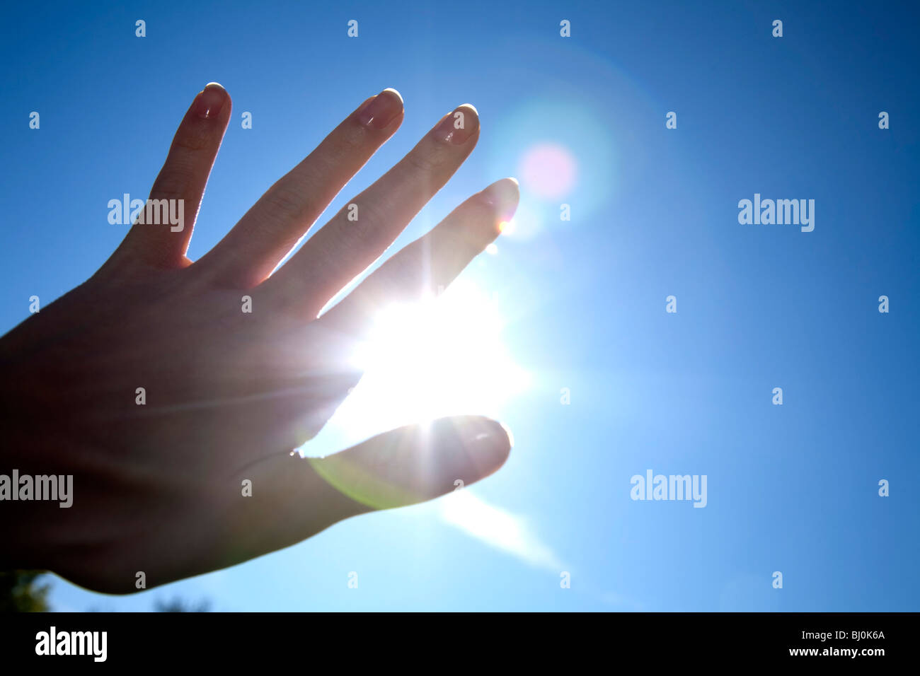 close-up of hand in front of blue sky with burning sun - Stock Image