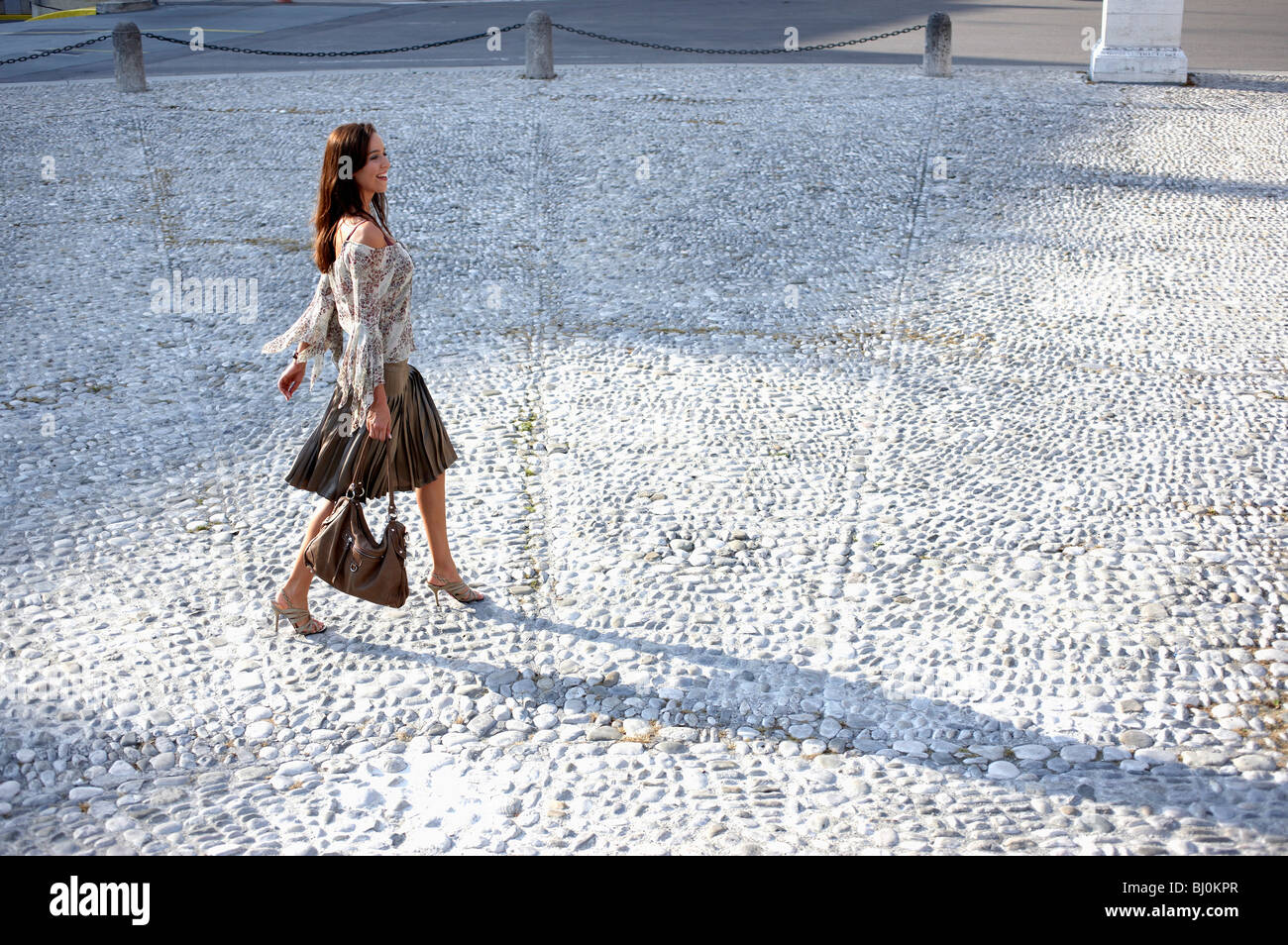 young woman walking over square in city - Stock Image