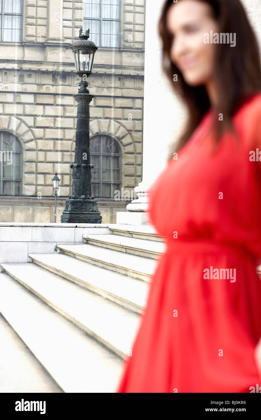 young woman in red dress standing in front of theatre Stock Photo