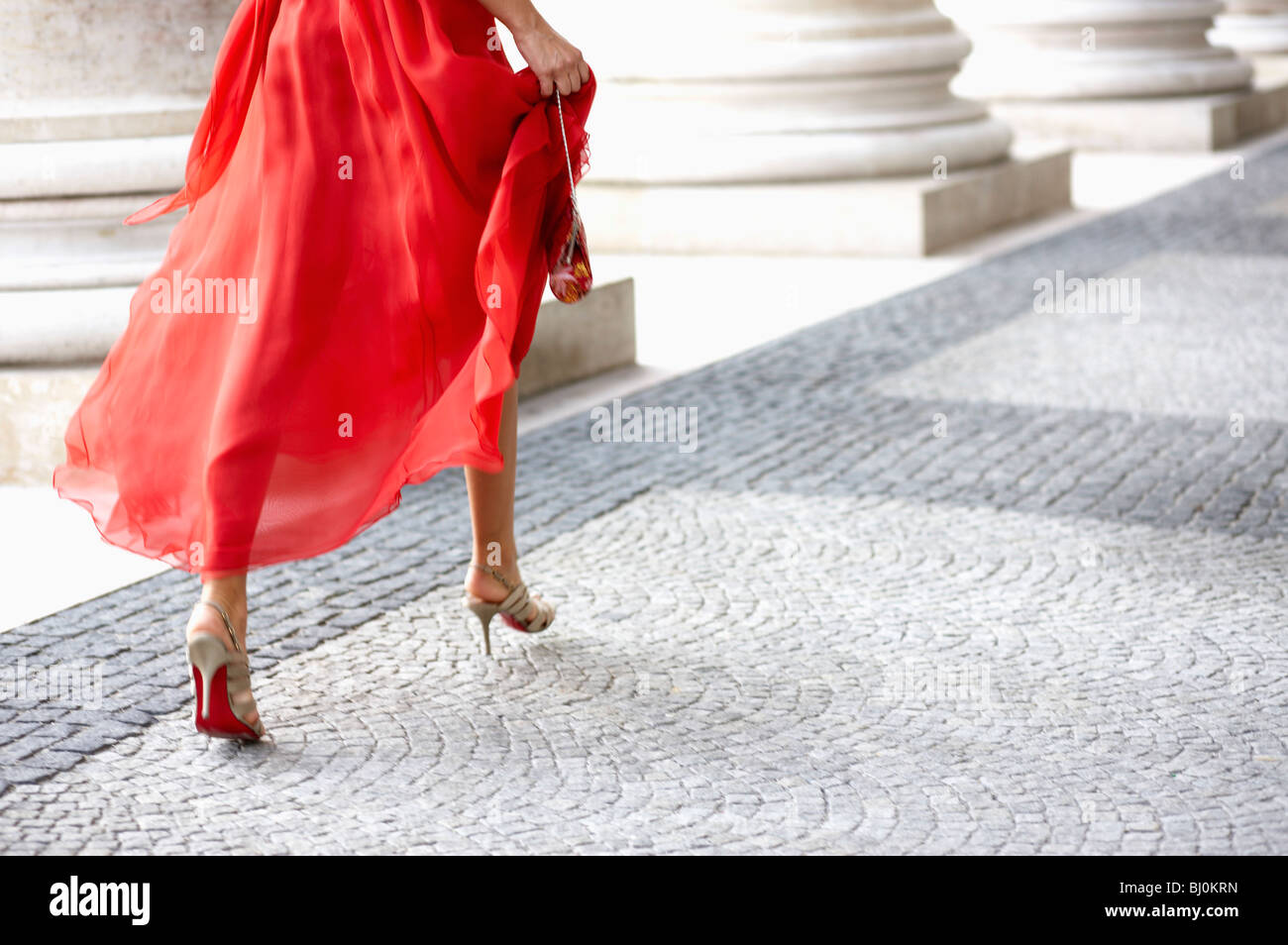 detail of young woman in red dress running through arcades of theatre - Stock Image