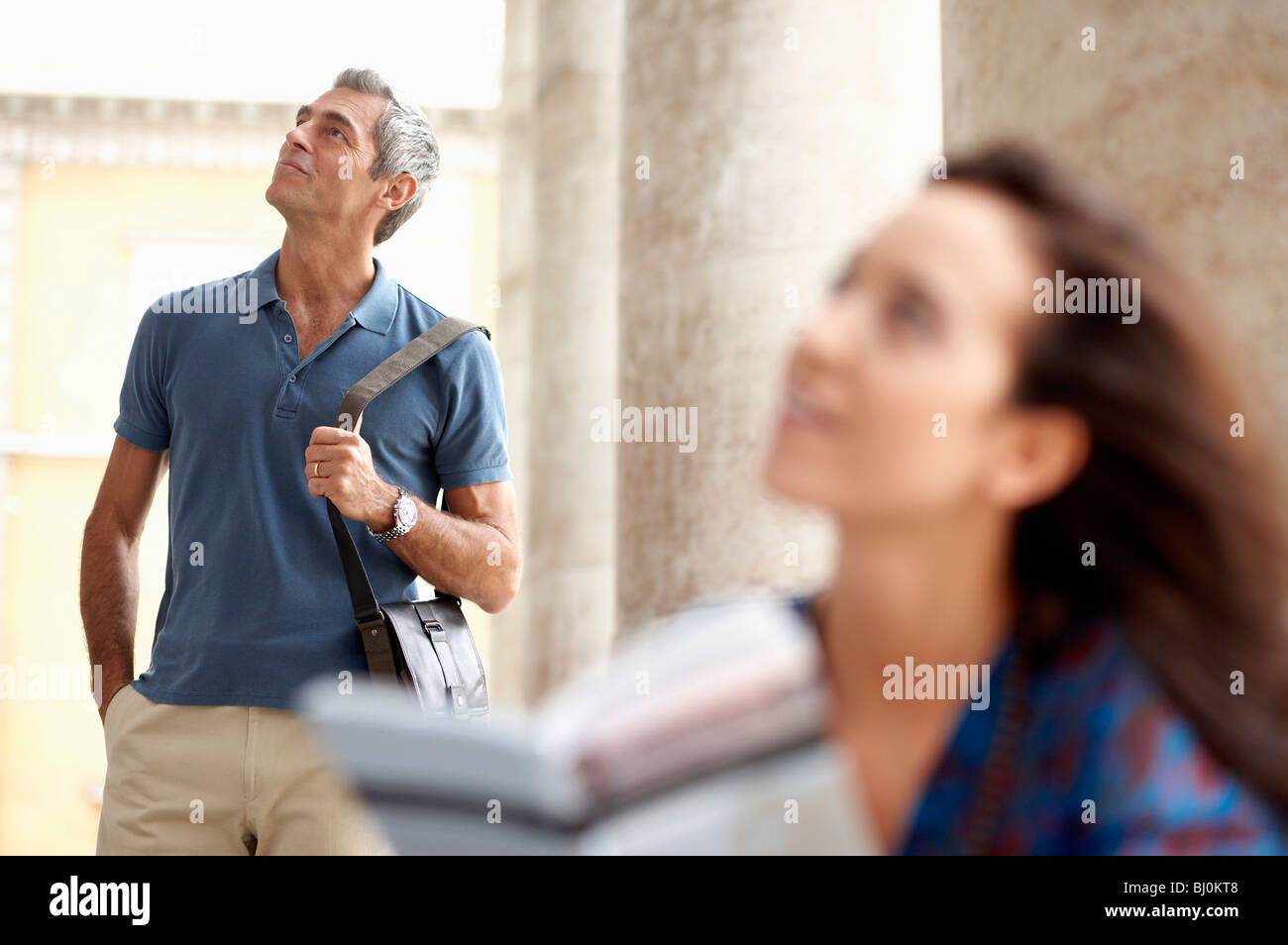 couple in city looking at object of interest - Stock Image