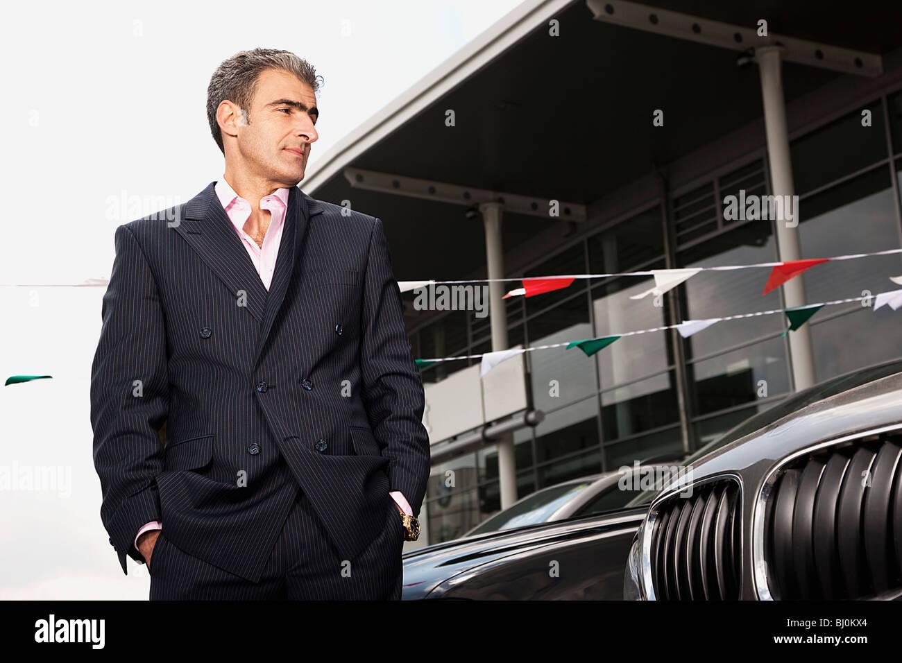 portrait of salesman at car dealer - Stock Image