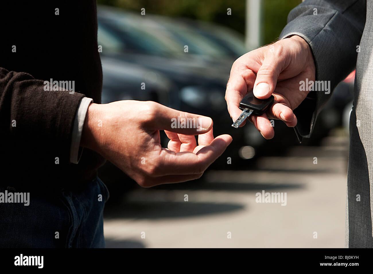 close-up of salesman at car dealer handing out car key to customer - Stock Image