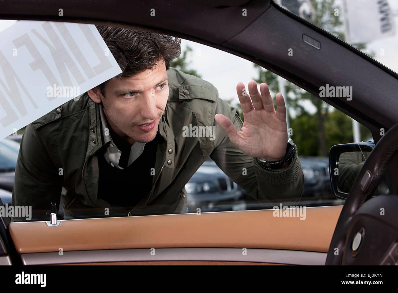portrait of man looking through car window - Stock Image