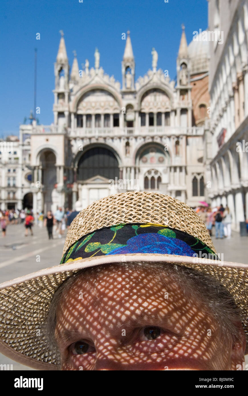 Venice Italy Woman tourist wearing straw hat St Marks Square. Piazza San Marco. Basilica San Marco in background. - Stock Image