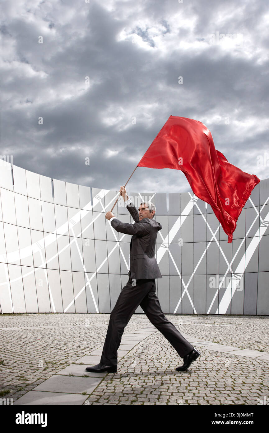 businessman waving red flag - Stock Image