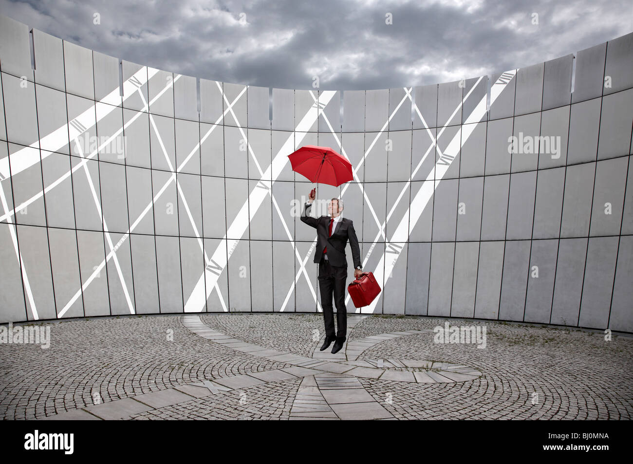businessman with red suitcase and umbrella jumping - Stock Image
