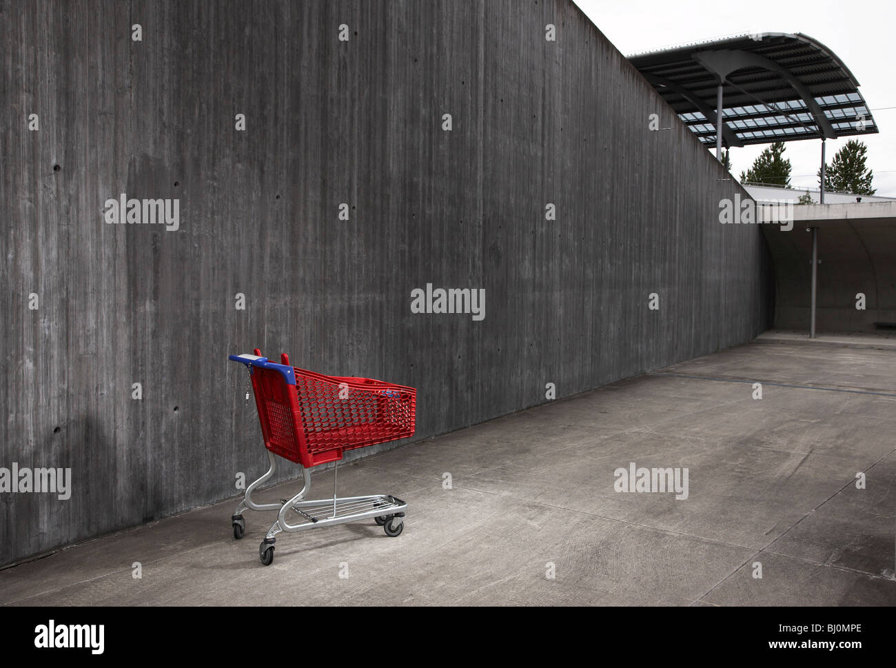 red shopping trolley in front of concrete wall - Stock Image