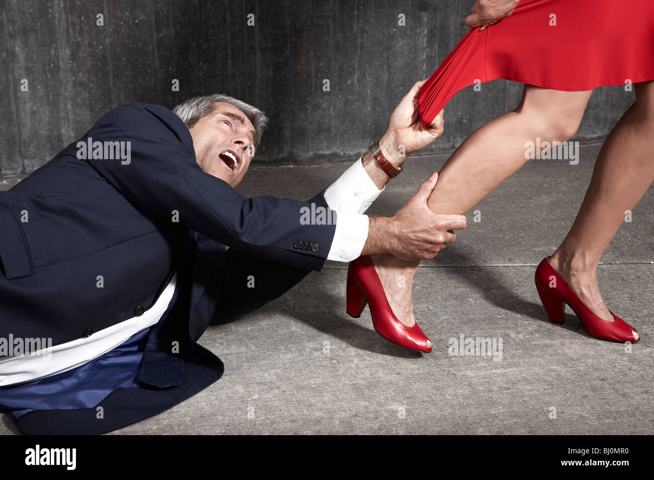 desperate man lying on floor trying to hold woman - Stock Image