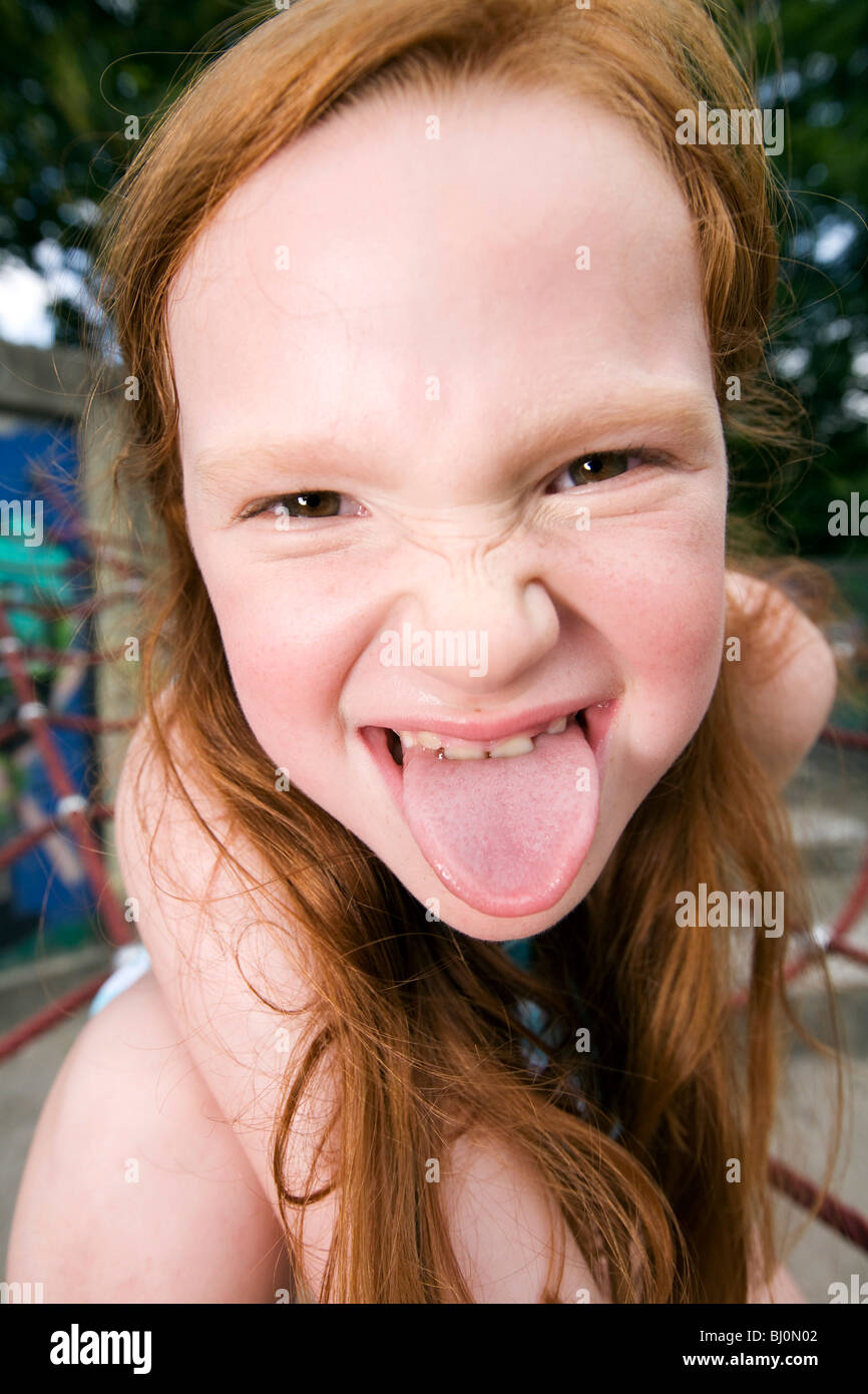 headshot of young girl sticking out tongue - Stock Image