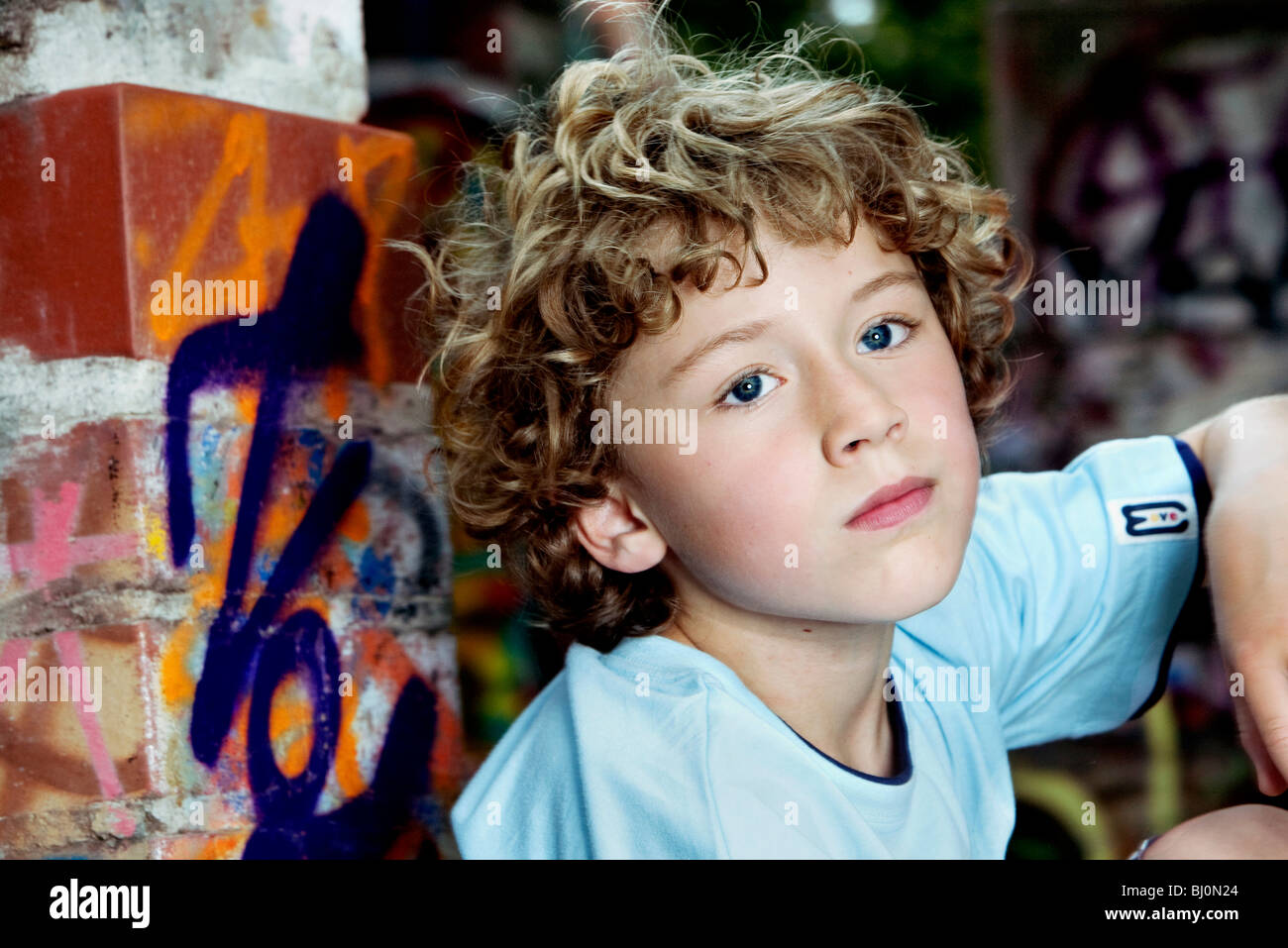 portrait of pensive young boy with curly hair - Stock Image