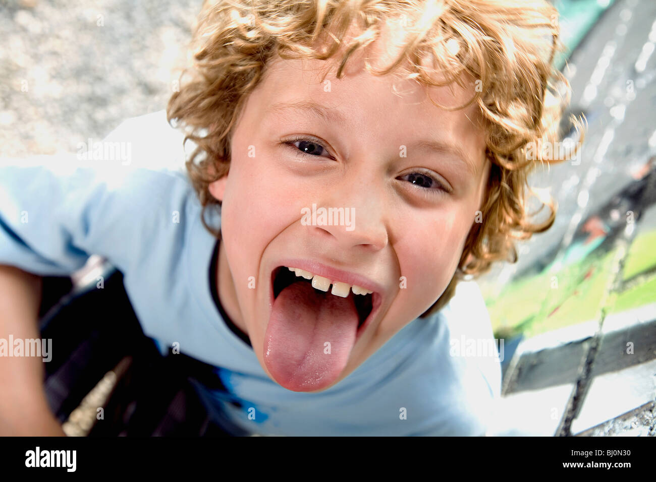 portrait of young boy sticking out tongue - Stock Image