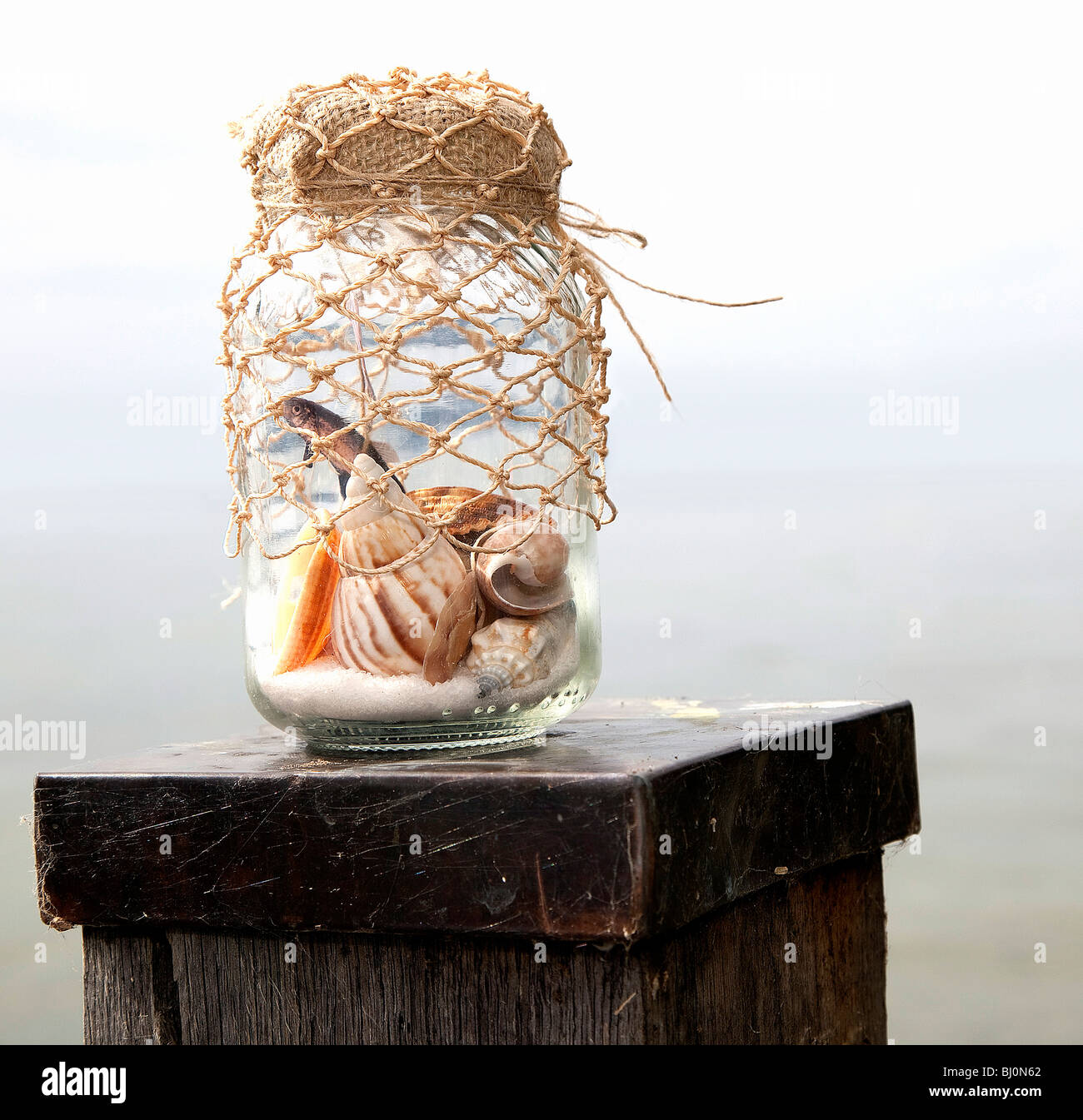 shells in jar on pole by the sea - Stock Image