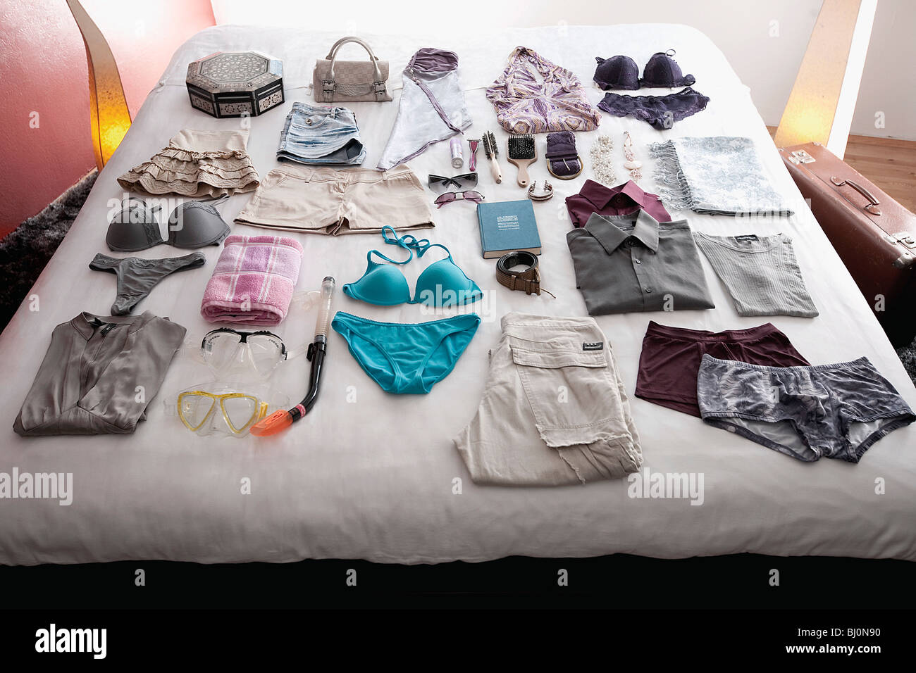 clothes for travel laid out on bed - Stock Image