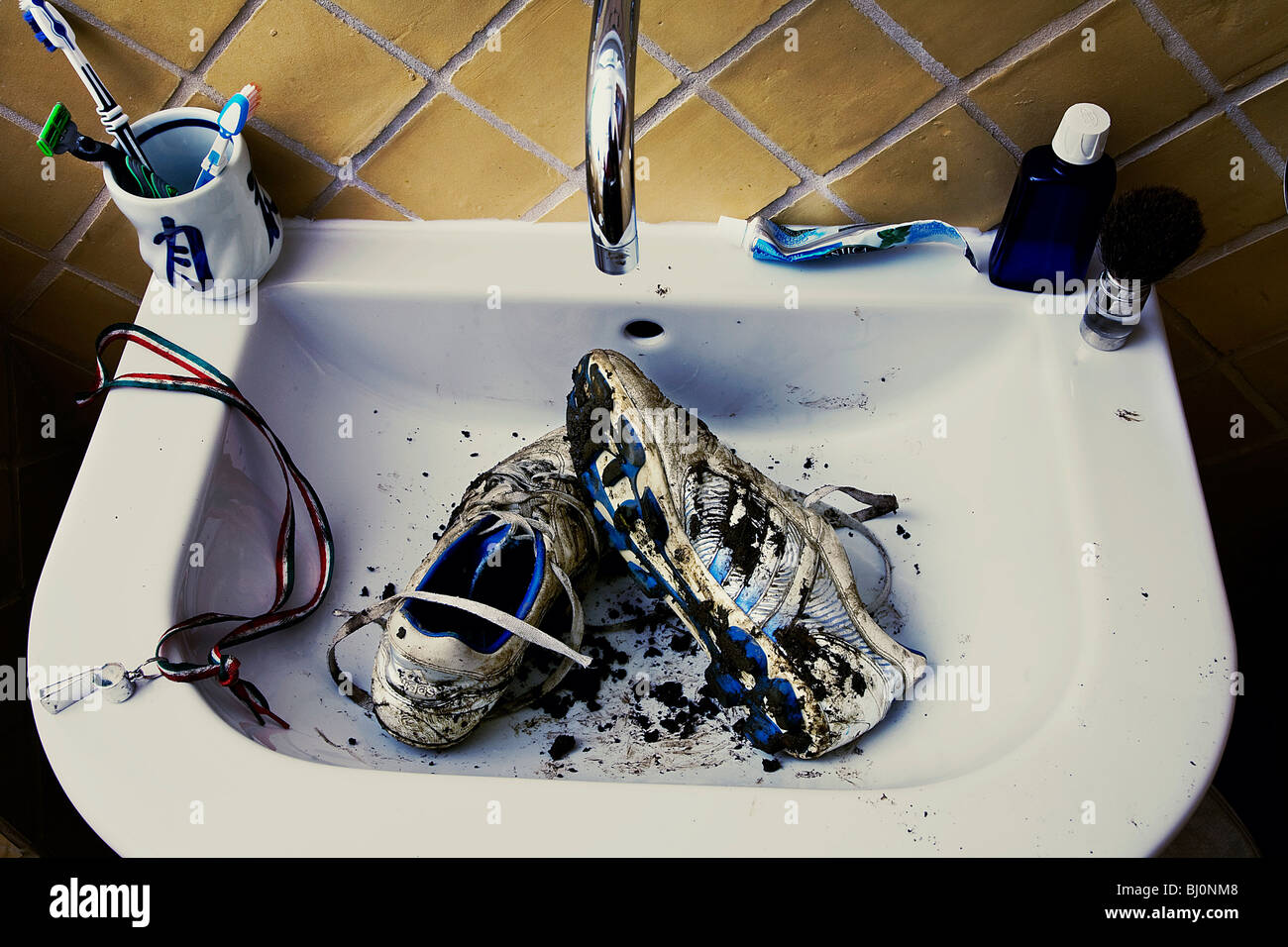 football boots in sink waiting to be cleaned - Stock Image