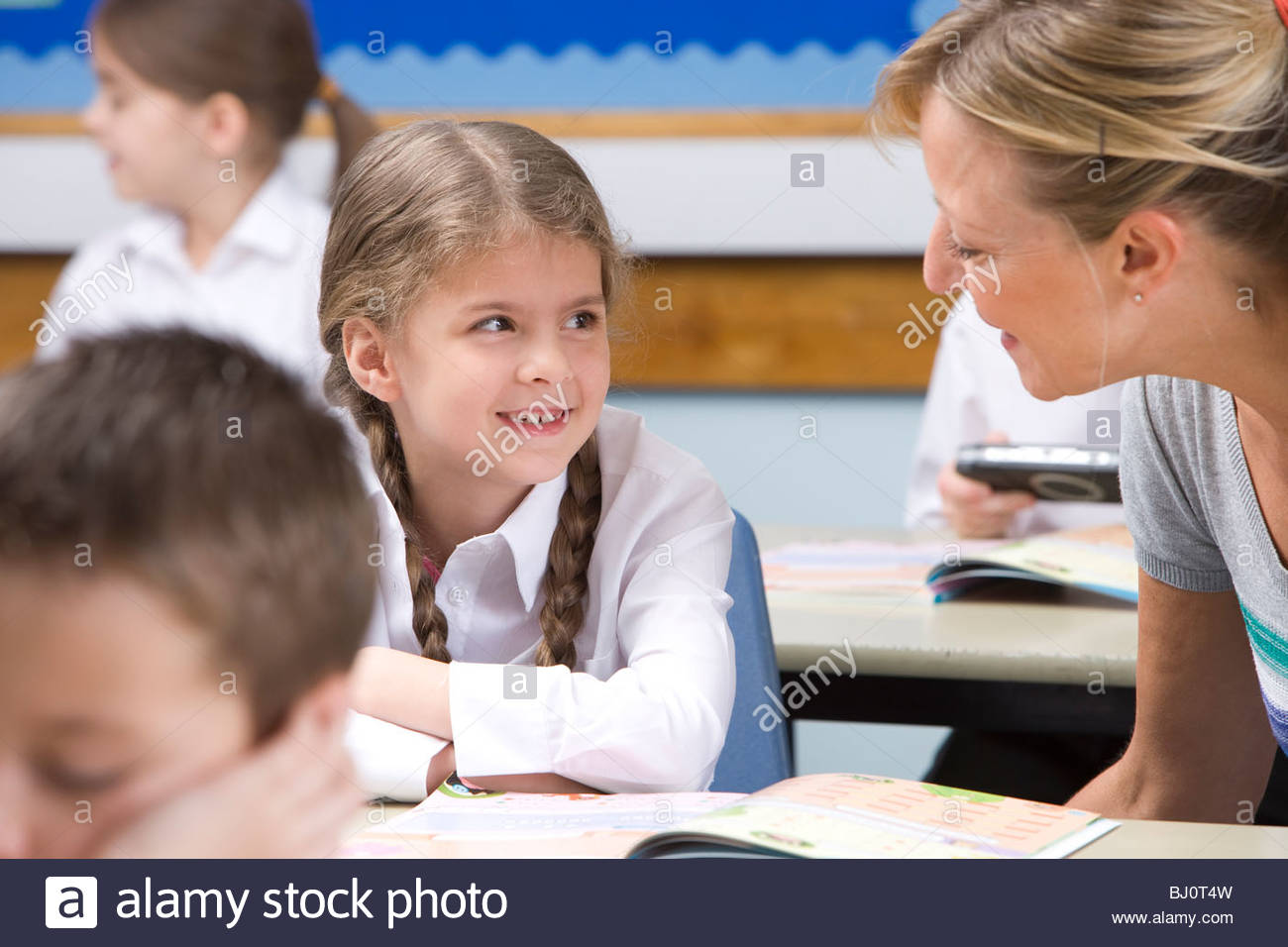 Teacher helping student with studies in classroom - Stock Image