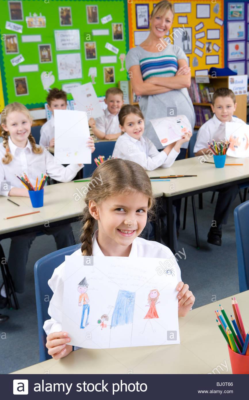 Proud school children showing off drawings in classroom - Stock Image