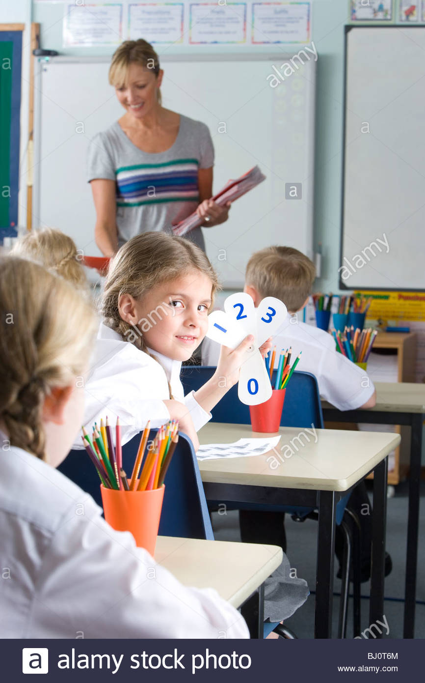 School girl holding number cards at desk in classroom - Stock Image