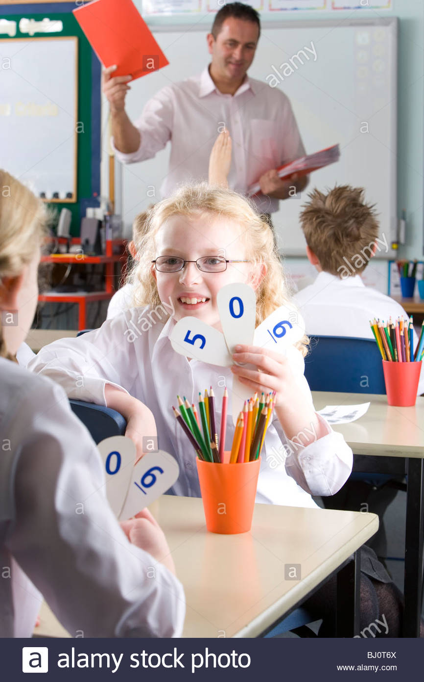 School girls holding number cards at desk in classroom - Stock Image