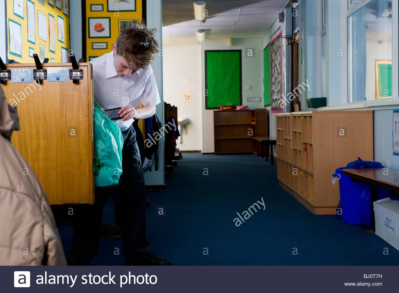 School boy taking something from bag in cloakroom - Stock Image
