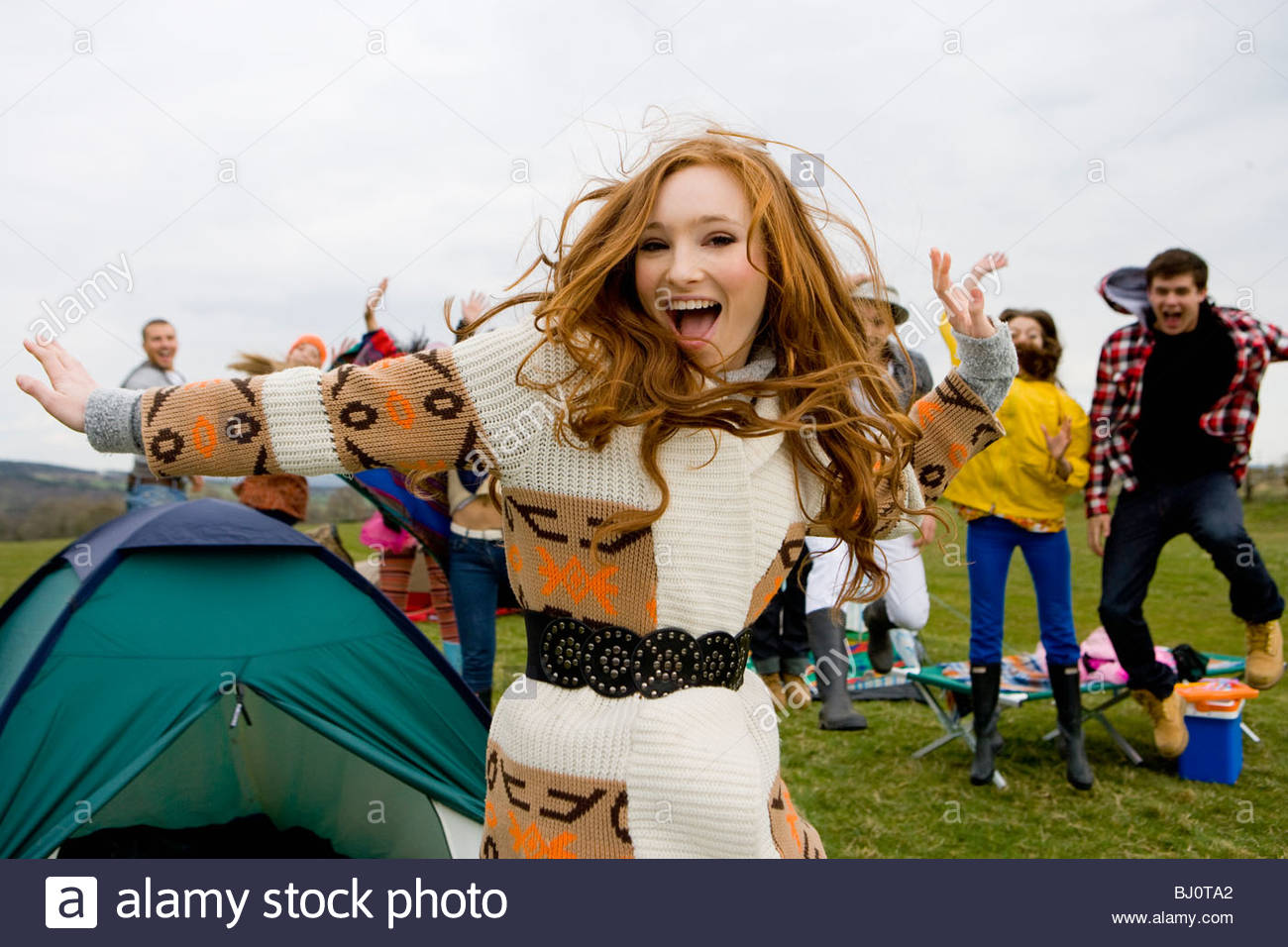 Excited friends camping and attending outdoor festival - Stock Image