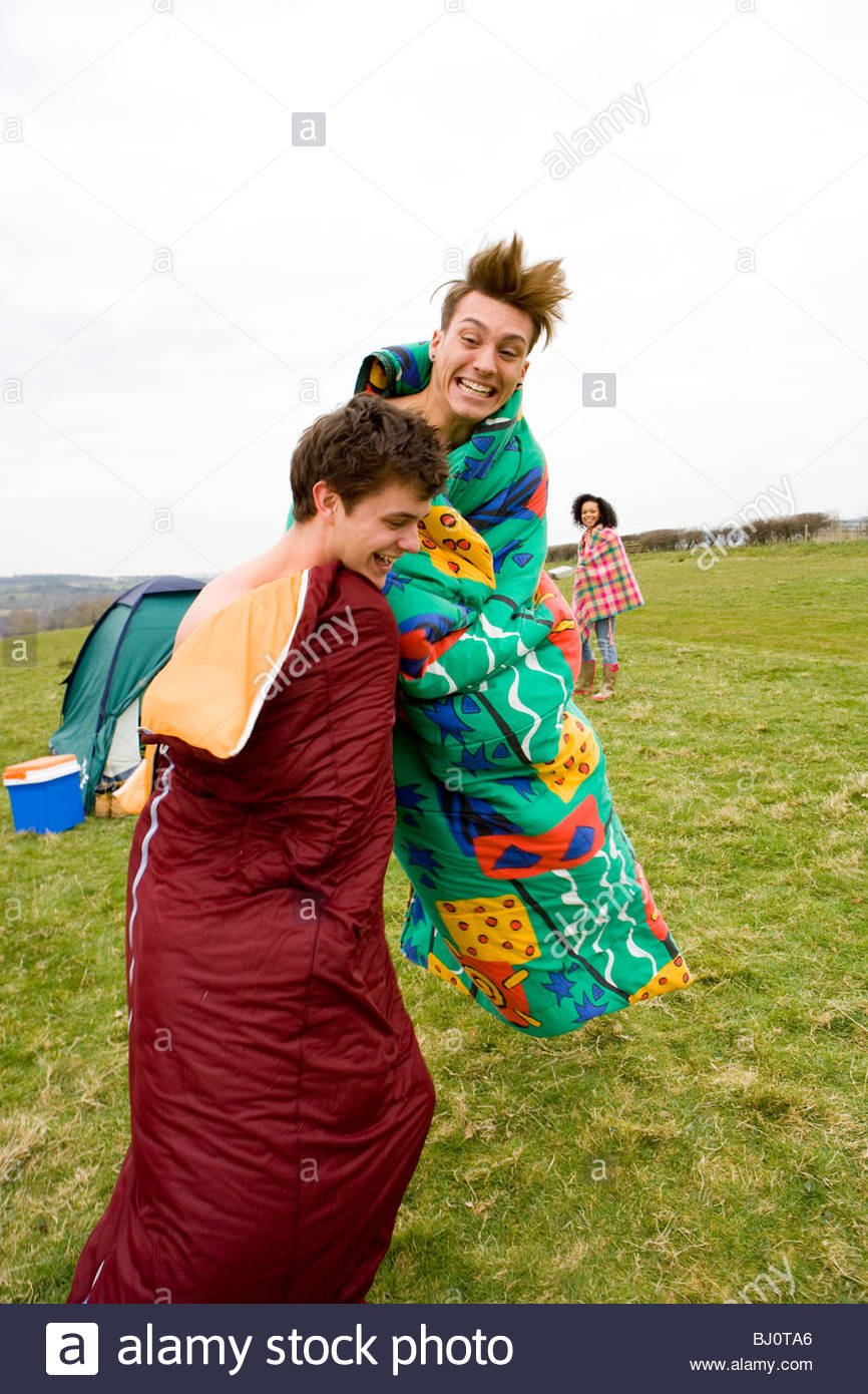 Excited men jumping in sleeping bags at outdoor festival - Stock Image