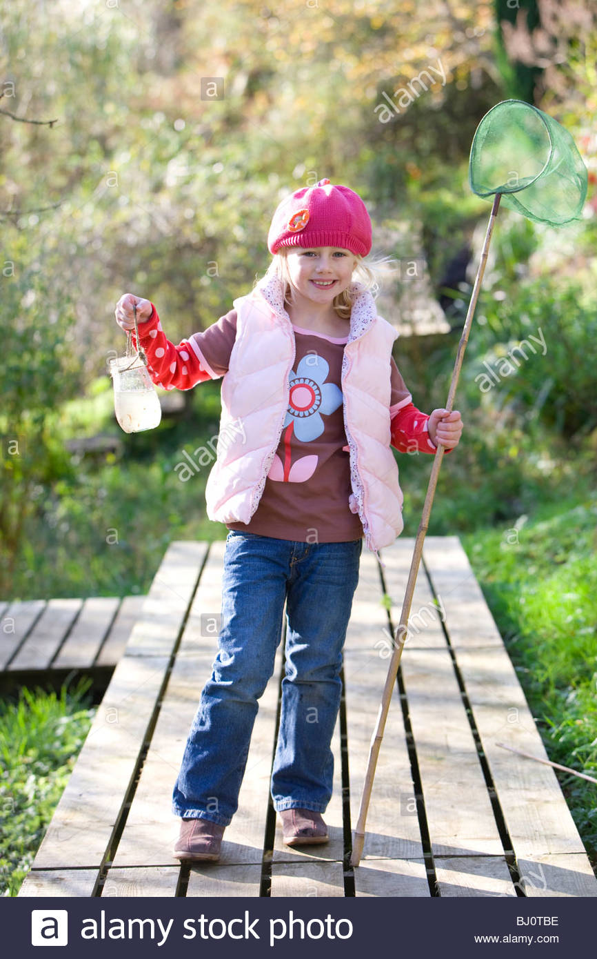 Smiling girl holding bug net and specimen jar outdoors - Stock Image