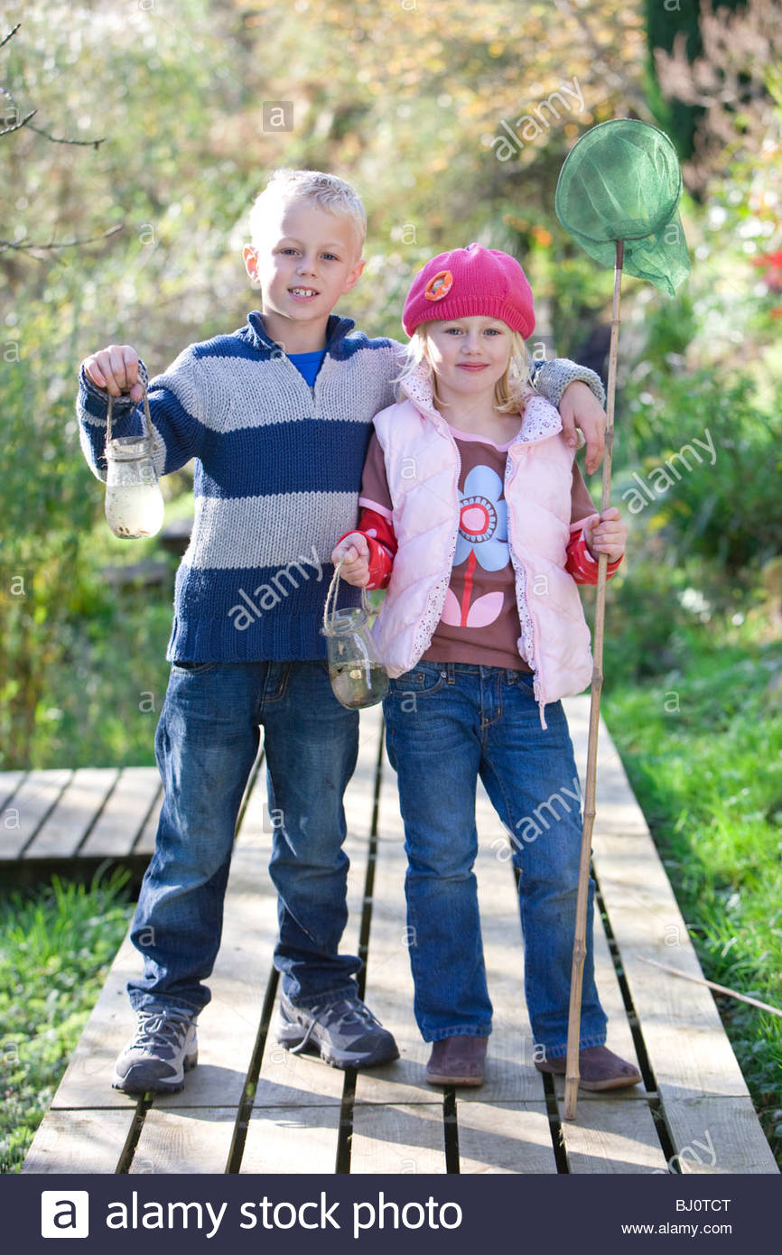 Brother and sister holding bug net and specimen jar outdoors - Stock Image
