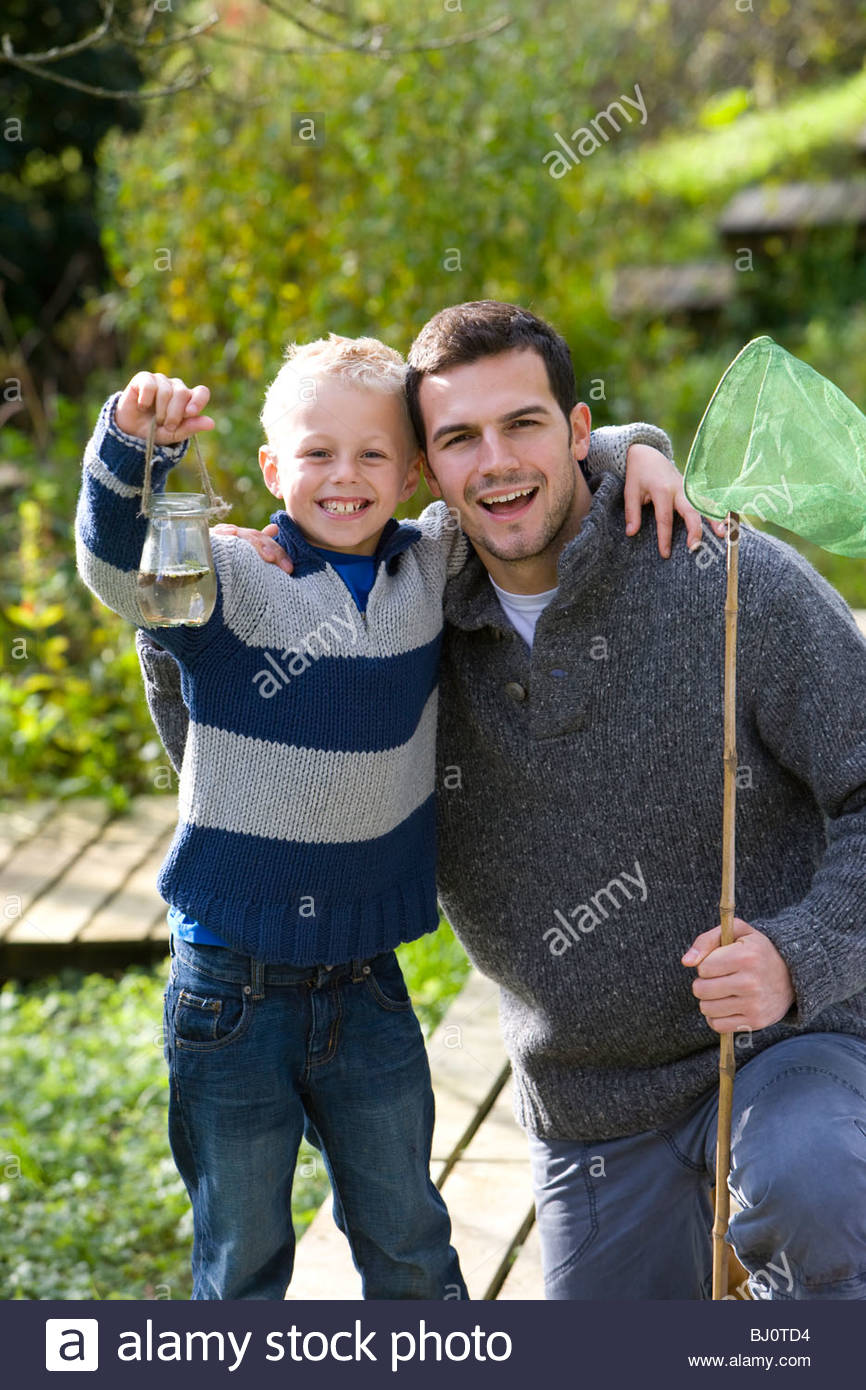 Father and son holding bug net and specimen jar outdoors - Stock Image