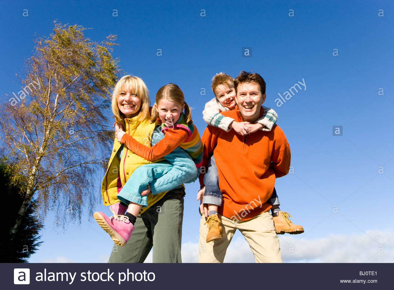Parents giving children piggyback rides - Stock Image