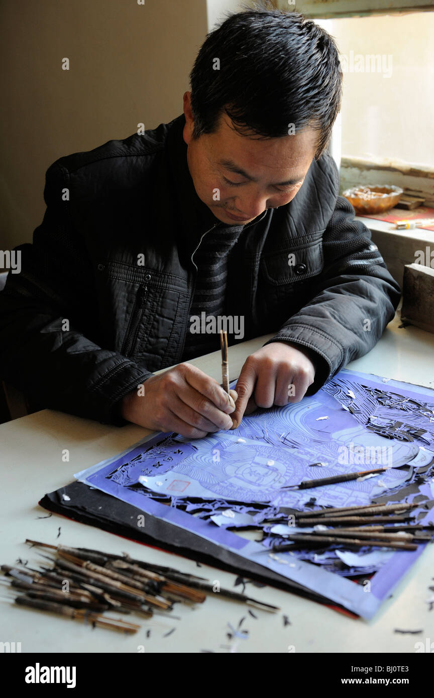 Ling Mande, a folk artist of Paper Cutting, is working in his studio in Yuxian county, Hebei province, China.02 Stock Photo