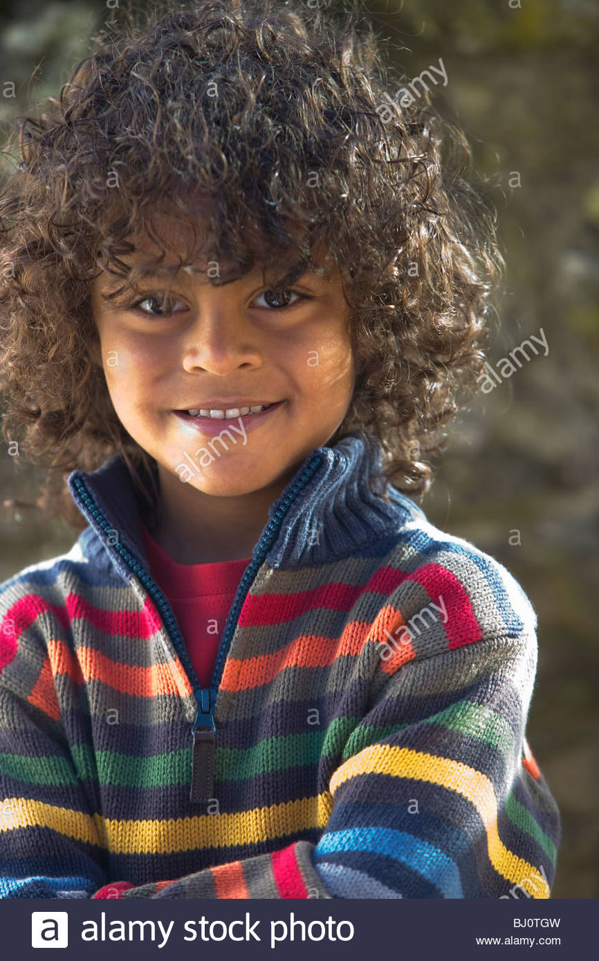 Smiling, curly haired boy in colorful sweater - Stock Image