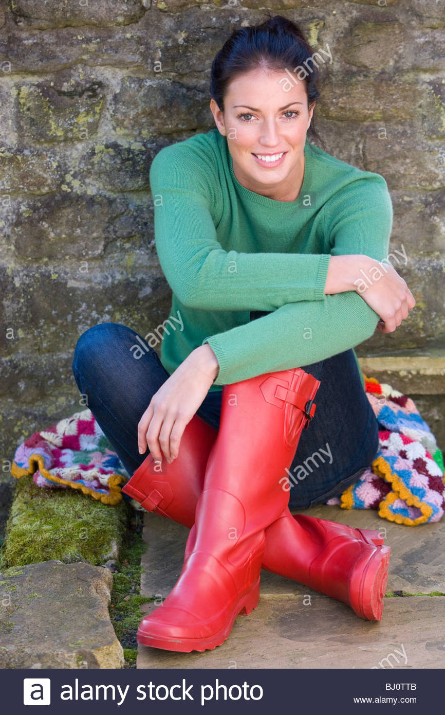 Smiling woman in rubber boots leaning against wall Stock Photo